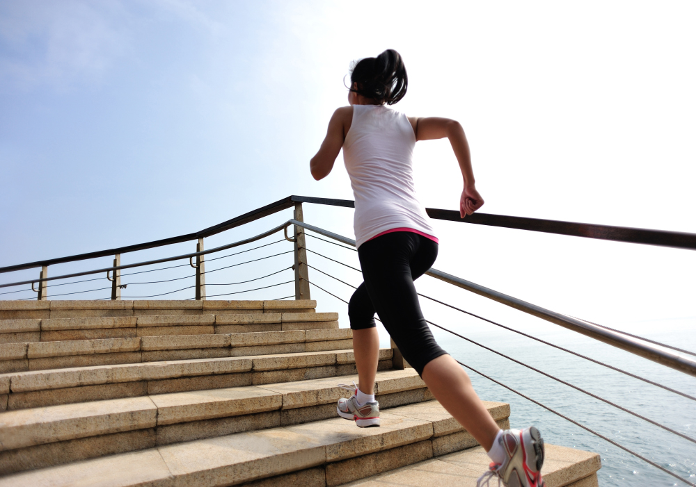 fitness woman running on stone stairs seaside
