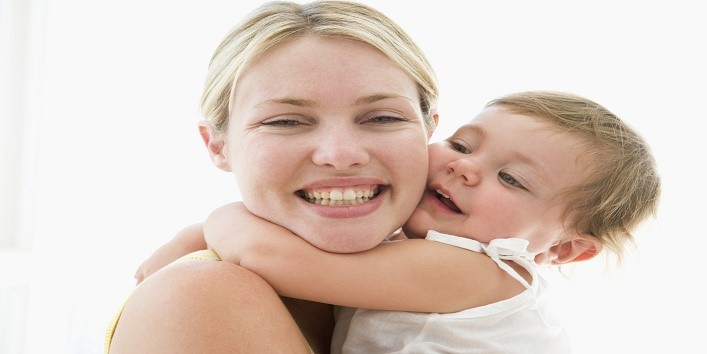 Mother and baby indoors hugging and smiling