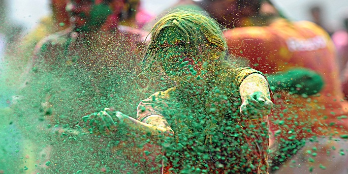 Indian woman play with coloured powder during Holi celebrations in Hyderabad on March 27, 2013.  Holi, also called the Festival of Colours, is a popular Hindu spring festival observed in India at the end of the winter season on the last full moon day of the lunar month.   AFP PHOTO/Noah SEELAM        (Photo credit should read NOAH SEELAM/AFP/Getty Images)