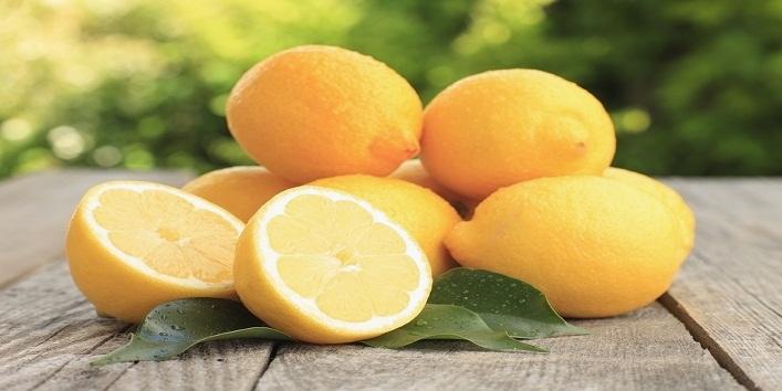 Fresh wet lemon with leaf on the garden table