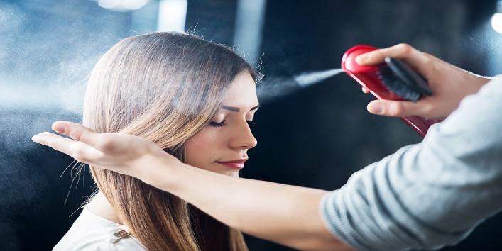 Hairdresser spraying his customer's hair.