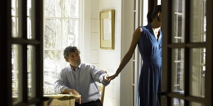 Mature man holding woman's hand, woman turning away