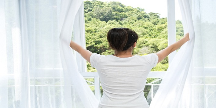 Asian young woman opening the curtains to a new day.