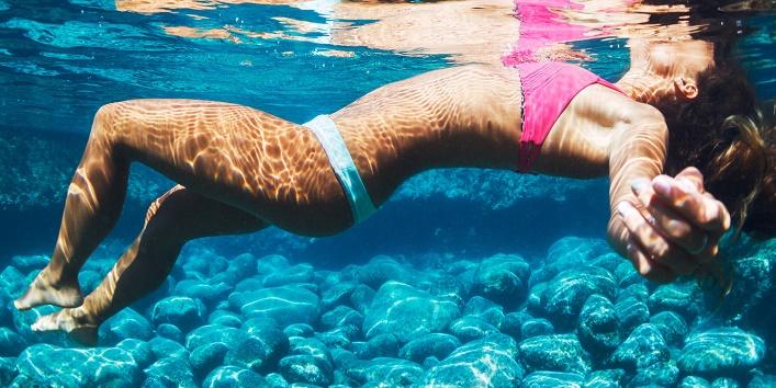 Beautiful Woman in Bikini Floating in Turquoise Colorful Water
