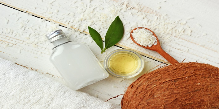 Coconut oil, milk, dried shavings, nut, towel, skincare ingredients. Top view white wooden background.