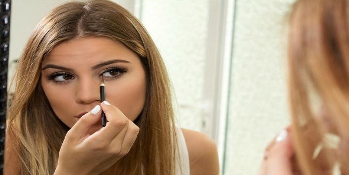 Teenage girl applying eyeliner on eyes
